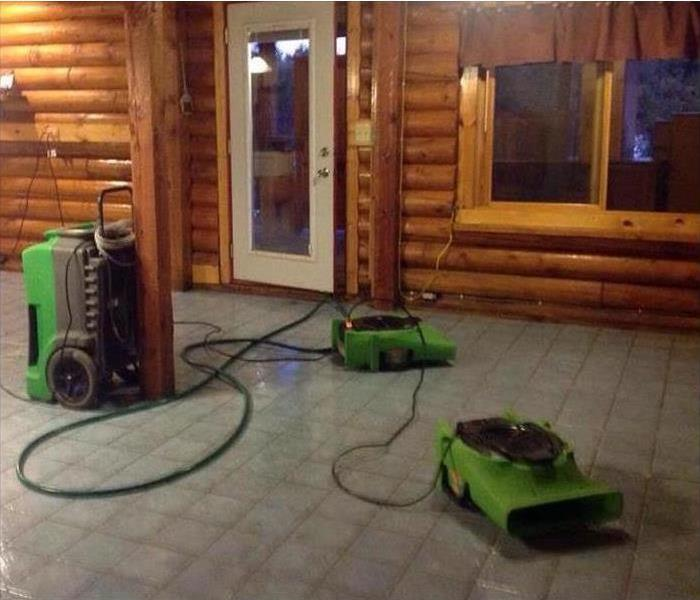 Wooden cabin with exposed tile floor and air movers.