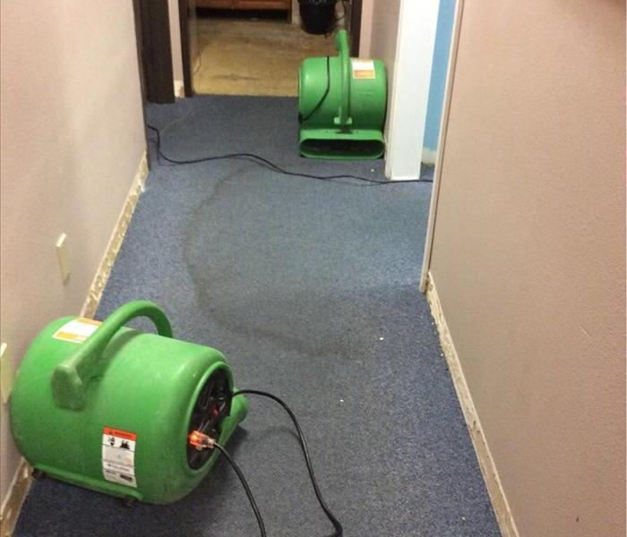 Two air movers in a hallway and a water stain on the carpet